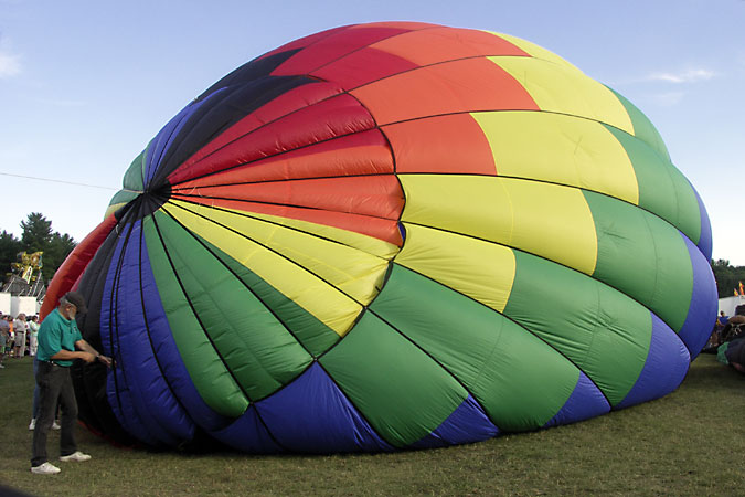 """The Hillsborough, New Hampshire balloon festival occurs every year in July, near Concord NH. For further information, see   <a href=""""http://www.balloonfestival.org/balloonhome.html"""">http://www.balloonfestival.org/balloonhome.html</a>. A balloon festival also occurs in Queechee, Vermont in June.<br /> <br /> One by one, the dozen balloons at the Hillsborough balloon festival prepared to ascend early Saturday evening. Eight liftoffs were planned for the festival but only 2-3 happened. The wind must be under 10mph because balloons are dependent upon the wind, and unable to steer. They can only control ascent and descent."""