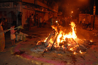 Bonfire lit on the night before the Holi festival of colours. Women from the area come and pray and make offerings into the fire. Its custom to bring stalks of wheat, barley & other grains which are lightly roasted and then taken as prasad for a prosperous year ahead.  Holi the Festival of Colours being celebrated in Jaipur, the Capital city of Rajasthan, India.