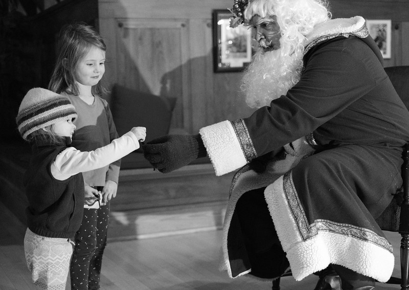 Justin Sheely | The Sheridan Press<br /> One-year-old Coraline hogarty-Dick, left, and sister Isla Hogarty-Dick receive bells from Father Christmas, by David Peterson, during the annual Holiday Open House Friday evening at the Trail End State Historic Site. The historic site commonly known as Kendrick Mansion is hosting open houses Saturday and Sunday, December 2 and 3 from 4 p.m. to 7 p.m. Events include live music, figgy pudding and a visit with Father Christmas.