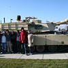 Mahmoud, Barbara, Arody, Lene, Mboyi, Hamzah, and Aqsa pose in front of a tank.
