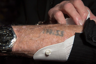 "Survivor Henry Flescher (89) shows off his tatoo. During the Holocaust, concentration camp prisoners received tatoos only at one location, the Auschwitz concentration camp complex.  He was born in Vienna Austria and initially escaped to France where he was eventually interred in Drancy deportation camp, a place where Jews, Gypsies, and others were held before being shipped to the German concentration camps. On the matter of the Vichy French, Henry simply says ""Petain gave me to Eichmann"". (photo by Jeff Malet)"