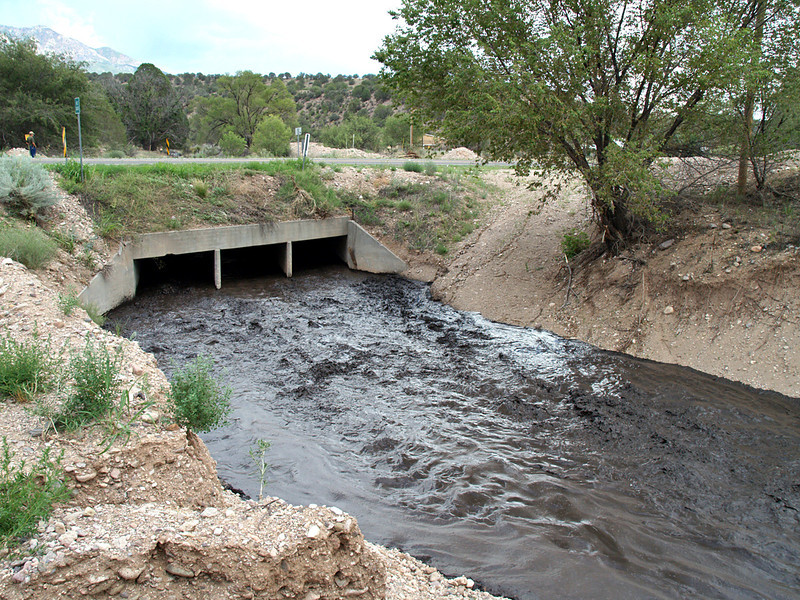 Photo taken the afternoon of Monday, Aug. 6th<br /> Holt Gulch as it passes under hwy 180 in Pleasanton, NM<br /> The flow is the result of rain up on the mountain.<br /> Black, smelly, goo is burn residue from the Whitewater-Baldy fire of May & June, 2012.