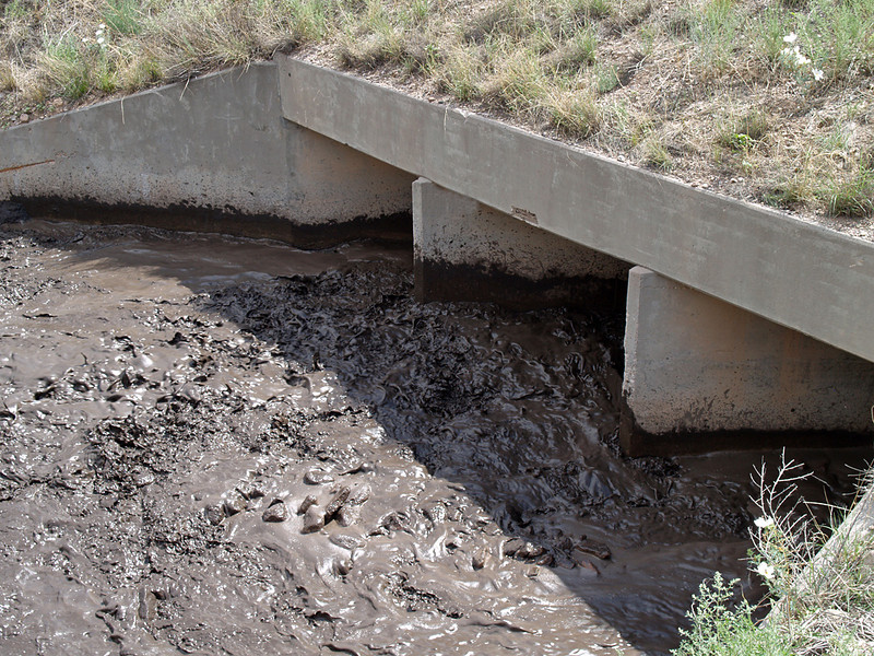 Photo taken the afternoon of Monday, Aug. 6th<br /> Holt Gulch as it passes under hwy 180 in Pleasanton, NM<br /> The flow is the result of rain up on the mountain.<br /> Black, smelly goo is burn residue from the Whitewater-Baldy fire of May & June, 2012.