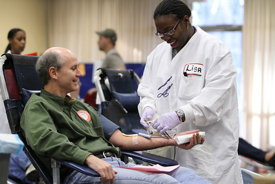 Kevin Melvin gets assistance from American Red Cross blood collection technician Melissa Gay as he completes his donation process. Melvin was one of 190 people who showed up to donate during the Dec. 11 blood drive at Holy Cross Church, Atlanta.