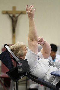 Carolyn Haynes holds her arm up after the needle has been removed. She saved her 18th blood donation for the Bob Buechner Blood Drive at Holy Cross Church, which was sponsored by the newly formed Blood Donation Ministry.