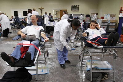 American Red Cross blood collection technician Lasha Carter, center, checks on Guillermina Coronado's blood bag as Brian Arnberger, left, reads during his donation process.