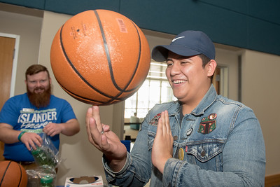 Paul Saldana spins a basketball on his hand at one of the many booths at the Homecoming Tip Off Picnic.