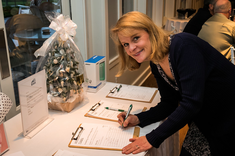 Julie Bujeaud makes a silent auction bid during the Homeless Center for Strafford County Spring Fling fundraiser event held at The Oaks in Somersworth Friday. [Scott Patterson/Fosters.com]