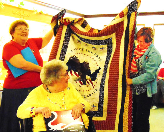 Debbie Blank | The Herald-Tribune<br /> Rivertown Quilters Club, Lawrenceburg, members Judy Sauerbrey (left) and Sheila Stevenson (right) present a Quilt of Valor they made to Mary Gargano.
