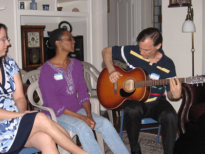 "Lisa singing ""Give me one reason"" as Bruce accompanies and Andrea looks on."