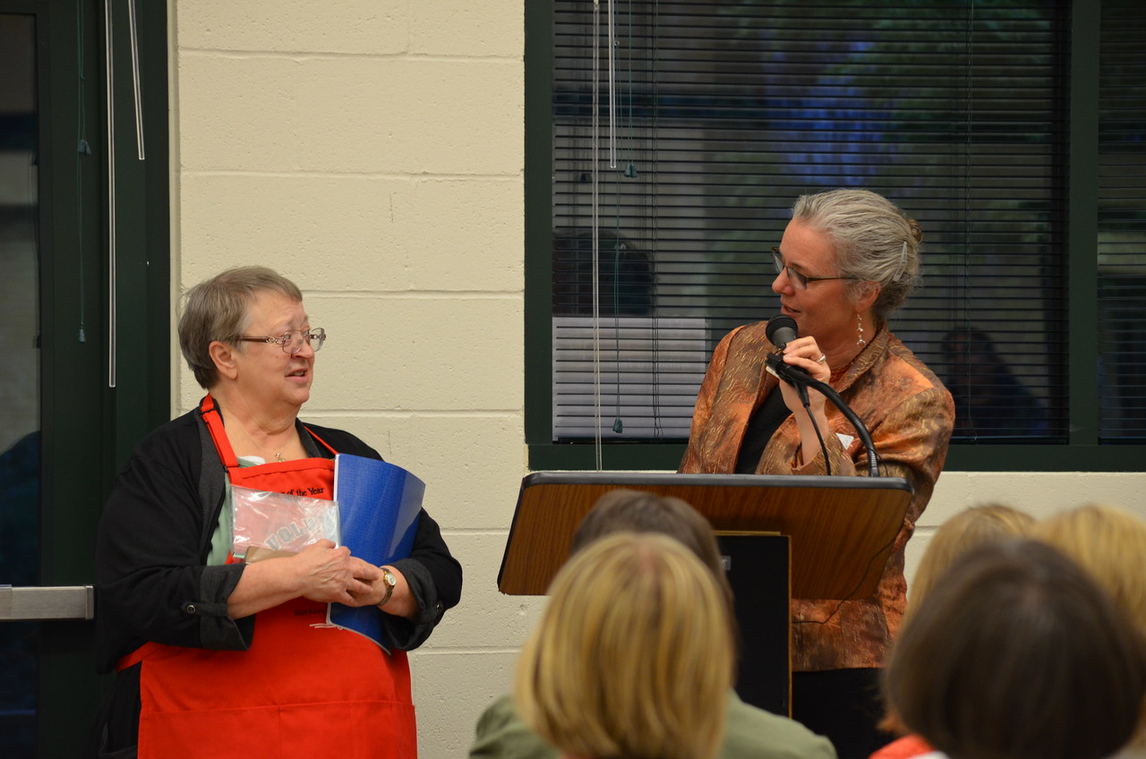 Barb Cash accepts the Volunteer of the Year Award and apron from BJ Andersen.