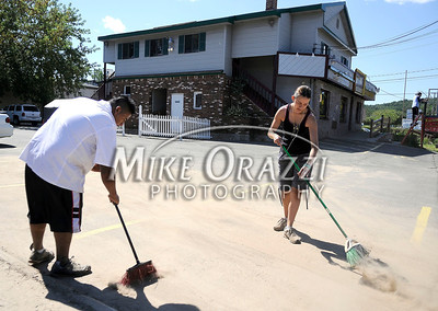 8/30/2011 Mike Orazzi | Staff David Santos and Gladys Botero clean up mud in the parking lot of the Latino Restaurant after the Pequabuck River rose past flood stage due to heavy rain brought on by Hurricane Irene.