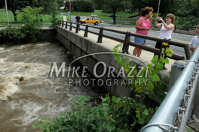 8/28/2011 Mike Orazzi | Staff Cousins Paula Baron and Sharon Fioretti photograph the Pequabuck River as it flows along Memorial Blvd. in Bristol after Hurricane Irene passed through Central Connecticut Saturday into Sunday.