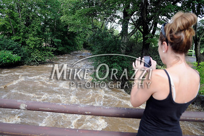 8/28/2011 Mike Orazzi | Staff Marla Pechulis photographs the Pequabuck River as it flows along Memorial Blvd. in Bristol after Hurricane Irene passed through Central Connecticut Saturday into Sunday.