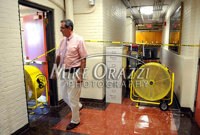 8/30/2011 Mike Orazzi | Staff Clara T. O'Connell School principal Mike Audette surveys the water damage in the lower level of the Bristol elementary school that borders the Pequabuck River.