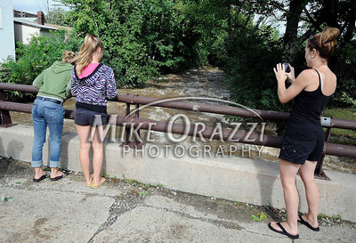 8/28/2011 Mike Orazzi | Staff Marla Pechulis photographs her twin daughters Madison and Olivia,13, and the Pequabuck River as it flows along Memorial Blvd. in Bristol after Hurricane Irene passed through Central Connecticut Saturday into Sunday.