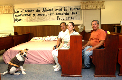 CCI members Leo Alcerro and his wife Nelby Gomez and their dog Neptune, a 9 month-old pitbull.  On the back pew is Rene' Maradiaga who is living in Houston, but came back to help repair the church.  They sit in the sanctuary of the church, which also serves as bedrooms for the two families staying at the church.  MORE STORY INFO: Two families are now living at Comunidad Cristiana Internacional (CCI) because the members have major damage to their homes. The church sanctuary has been turned into sleeping quarters during the week and changed again for worship service.
