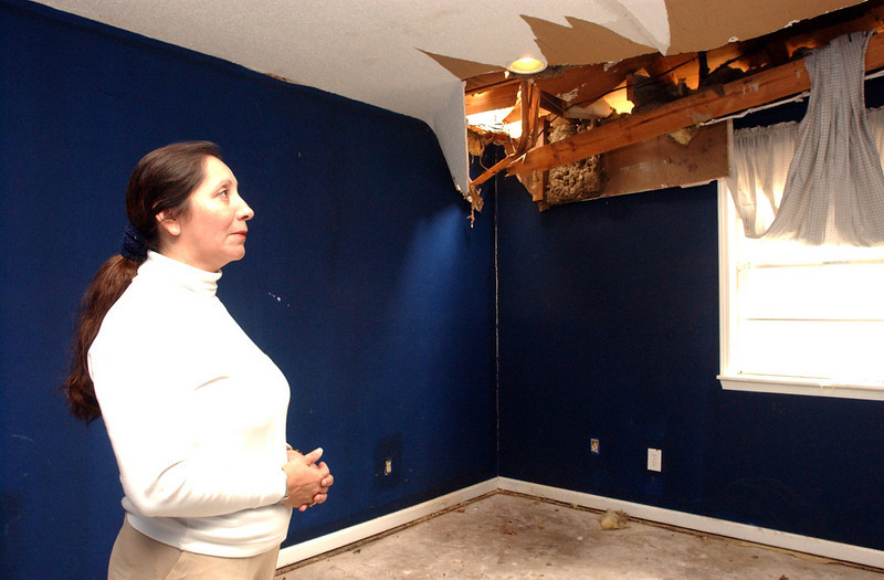 CCI church member Nelby Gomez stands in her son's room, where a tree from her neighbor's backyard came crashing through the corner of the house during Hurricane Katrina.  The house sustained roof and water damage. They have had to take portions of the walls out due to water damage.  Her husband, Leo Alcerro, works during the day, so Nelby goes to the house during the day to clean.   Her family, including 2 sons and 1 daughter, is living at the church.