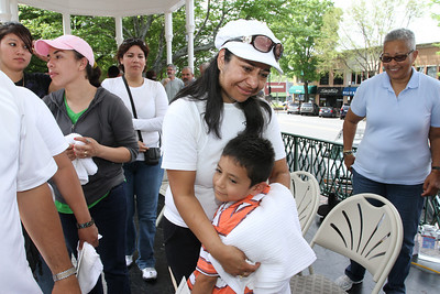 Maria Rios tries to fight back tears as her seven-year-old son Santiago comes up to hug her following the foot washing and prayer service. Like many others who had their feet washed, she is currently on the list for deportation proceedings.