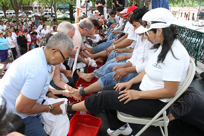 Twelve immigrants, some wearing ankle monitors, had their feet washed by American-born individuals to highlight the Pilgrimage For Immigrants prayer service on Holy Thursday. On the end Pauline Bullard-Moore, left, washes the feet of Mexican native Maria Rios.