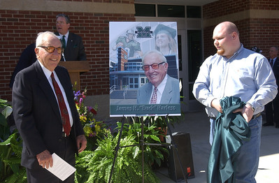 """Businessman and philanthropist James H. """"Buck"""" Harless of Gilbert, W.Va., joined Marshall University's Board of Governors in dedicating the Harless Dining Hall on MU's Huntington campus March 10, 2004. Here he unveils a commemorative poster."""