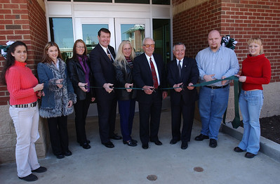 """Businessman and philanthropist James H. """"Buck"""" Harless of Gilbert, W.Va., joined Marshall University's Board of Governors in dedicating the Harless Dining Hall on MU's Huntington campus March 10, 2004. Here, he (4th from right) assists with the ribbon cutting."""