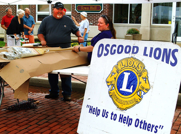 Debbie Blank | The Herald-Tribune<br /> Osgood Lions first Vice President Gary McCoy (left) and Keri Johnson sell brooms as a fundraiser and publicize their Oct. 8 bake sale and Yeti raffle at the Osgood party.