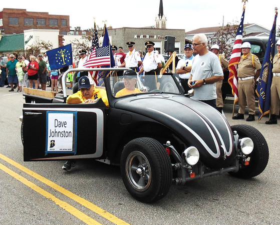 Diane Raver | The Herald-Tribune<br /> As torch bearer Dave Johnston (from left) arrives downtown in a 1969 Volks Rod driven by Greg Lindenmann, he is greeted by Bill Flannery.