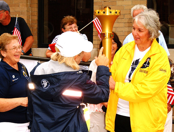 Debbie Blank | The Herald-Tribune<br /> Milan torchbearer Donna Barton (right) gets briefed by two Indiana Bicentennial Torch Relay volunteers.