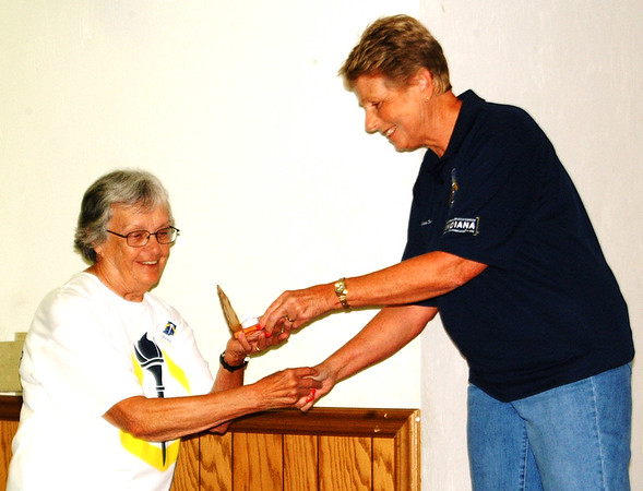 Debbie Blank | The Herald-Tribune<br /> Sunman torchbearer Viola Bruns (left), participating in memory of late husband Carl Bruns, accepts a candle holder gift from volunteer Janice Wilson at the evening's ceremony at the Milan VFW hall.