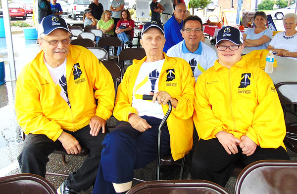 Diane Raver | The Herald-Tribune<br /> In spite of the rain, torch bearers Dave Johnston (from left), Ace Moorman, Mike Fritsch and Jon Kuntz were all smiles.