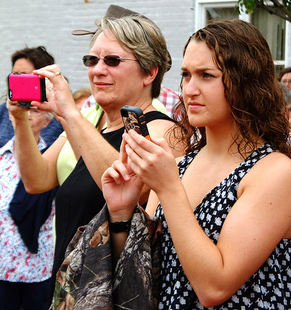 Debbie Blank | The Herald-Tribune<br /> Martha Kessens (left), Osgood, and Emily Cumberworth, Holton, take photos at the Osgood celebration. Kessens was there because her late dad, Sherman Lemen, was named a torchbearer and Cumberworth because brother Ethan and grandpa Melvin Meisberger were torch relay drivers.