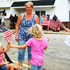 Debbie Blank | The Herald-Tribune<br /> Milan '54 Hoosiers Museum employee Susan Cottingham (from right) passes out flags to Tina Fryman, Dillsboro, and daughters Lauren, 6, Emily, 2, and Morgan, 3.