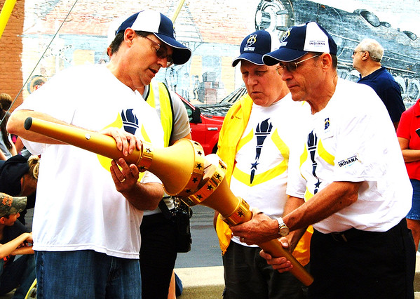 Debbie Blank | The Herald-Tribune<br /> Osgood torchbearers (from left) Larry Lemen, Wayne Peace and Owen Menchhofer pass the flame from one torch to another.