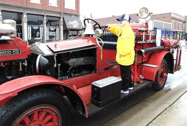 Diane Raver | The Herald-Tribune<br /> Jon Kuntz rings the bell on the 1921 fire truck he would later be riding in to carry the torch.