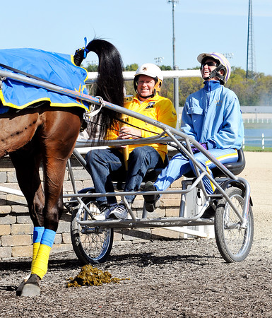 John P. Cleary   The Herald Bulletin<br /> Indiana Bicentennial Torch Relay torchbearer Jimmie Howell smiles as Hoosier Park driver/trainer Brooke Nickells reacts to her horse's deposit as they prepare to carry the torch around the Hoosier Park track.