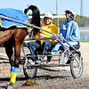 John P. Cleary | The Herald Bulletin<br /> Indiana Bicentennial Torch Relay torchbearer Jimmie Howell smiles as Hoosier Park driver/trainer Brooke Nickells reacts to her horse's deposit as they prepare to carry the torch around the Hoosier Park track.