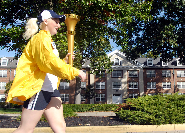 John P. Cleary | The Herald Bulletin<br /> AU senior Trisha McHugh, 21, carries the torch along University Blvd. through campus as the second torchbearer of the relay. The chemistry major is from Rockford, Illinois.