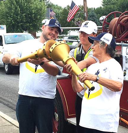 Photo courtesy of Julie Brock<br /> In Sunman Kyle Brock, grandson of John Campbell, passes the flame to Viola Bruns, representing her husband, the late Carl Bruns.