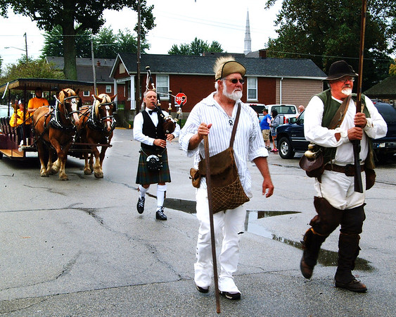 Debbie Blank | The Herald-Tribune<br /> National Muzzle Loading Rifle Association members in period costumes and a bagpiper led the Indiana Bicentennial Torch Relay into Versailles Saturday, Sept. 17. Torchbearer Jerry Wilson rode on a Vogt horse-drawn wagon.