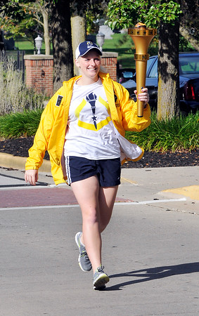 John P. Cleary   The Herald Bulletin<br /> AU senior Trisha McHugh, 21, carries the torch along University Blvd. as the second torchbearer of the relay. The chemistry major is from Rockford, Illinois.