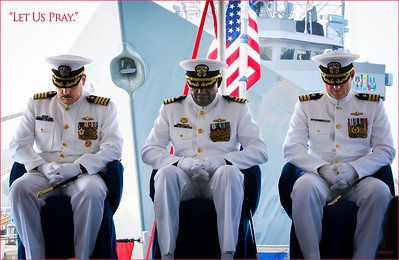 With warship and flag behind them, these servant leaders pause for the Invocation of Prayer