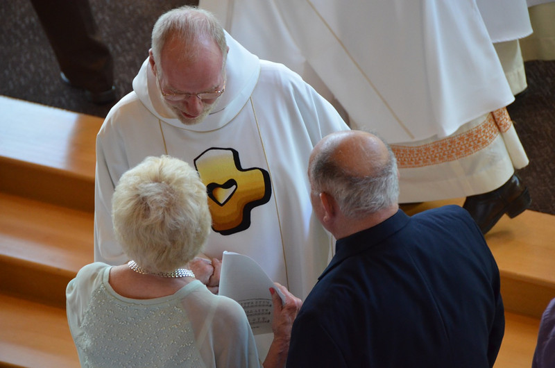Fr. Ed shares the sign of peace with Fr. Steve's parents