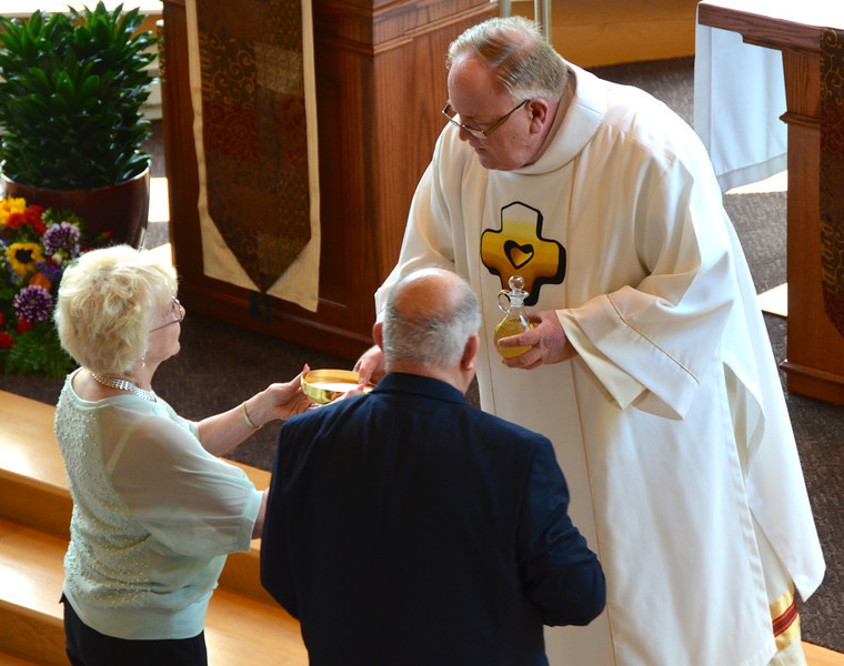 Fr. Steve's parents bring up the gifts. Dn. David Nagel, province treasurer, receives them.