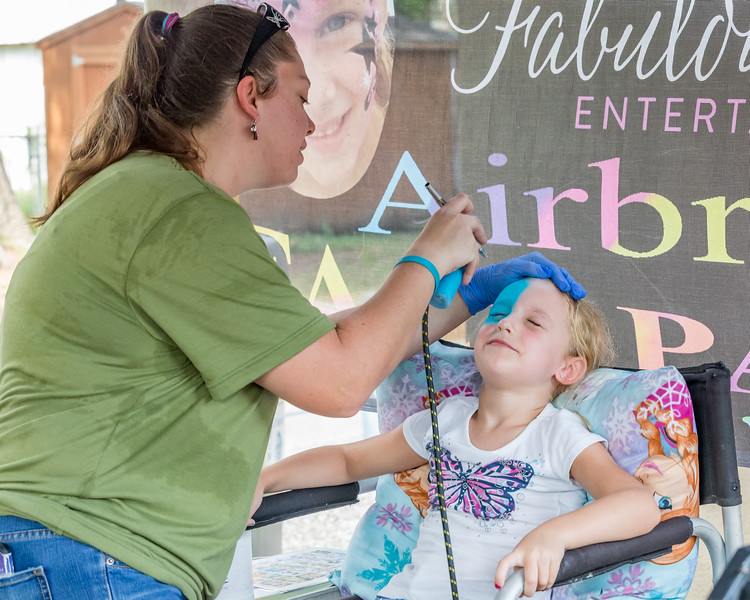 Nova Shover, 6, of Interlachen gets her face airbrushed with a patriotic theme at the July 4 celebration in Interlachen Thursday. Fred Broschart, Palatka Daily News