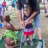 Danny Lewis helps Chastity Lewis, 3, putt while they play miniature golf at the Interlachen Independence Day Celebration. Fran Ruchalski/Palatka Daily News