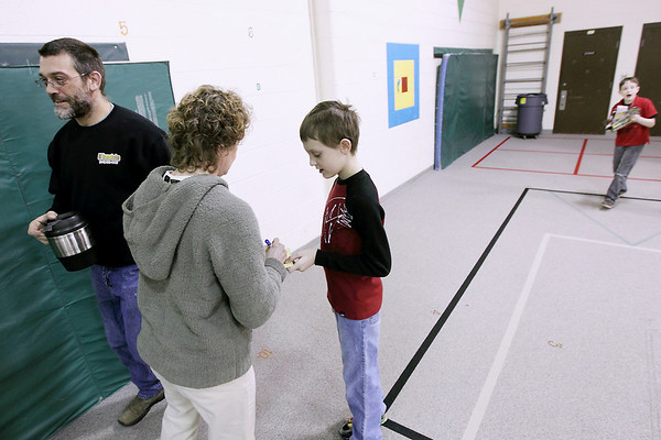 Record-Eagle/Keith King<br /> Mileage Club walkers Vince Canale, of Interlochen, and his son Vincent Canale Jr., have their Mileage Club cards marked Tuesday, March 1, 2011 at Interlochen Elementary School.  Each lap taken in the school, a quarter mile, is marked off on an individual's Mileage Club card. Since winter of 2007 the group has walked the equivalent of the Earth's circumference, approximately 24,900 miles.  Destinations are chosen for the walking program and the distance from the chosen location (this year it's Nome, Alaska) and Interlochen Community School is the Mileage Club's goal for distance walked in the school.