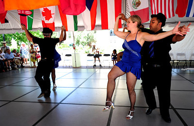 "Jenny Martin dances with her husband, Carlos Martin, both of Erie. The dance is part of a cuban style salsa called ""Rueda de Casino"" as part of the Los Casineros salsa group at the International Festival on Pearl St. Mall Saturday afternoon.  Rachel Woolf/ For the Camera"