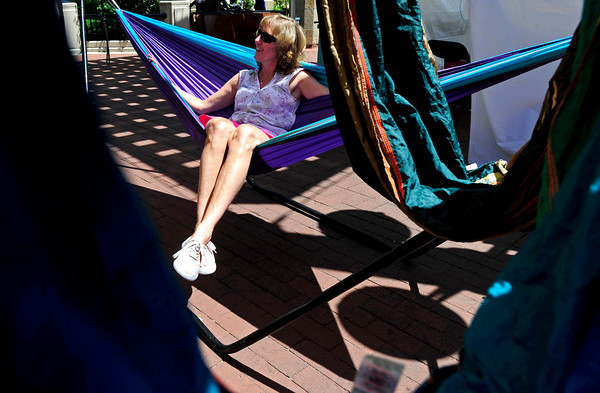 Gina Guthrie, of Arvada relaxes in a hammock of her own business, Gina Guthrie Designs at the International Festival on Pearl St. Mall Saturday afternoon.  Rachel Woolf/ For the Camera