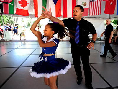 "Fatu Diebate Martin, 9 twirls with her father Carlos Martin, both of Erie. The twirl is part of a cuban style salsa called ""Rueda de Casino"" as part of the Los Casineros salsa group at the International Festival on Pearl St. Mall Saturday afternoon. Rachel Woolf/ For the Camera"